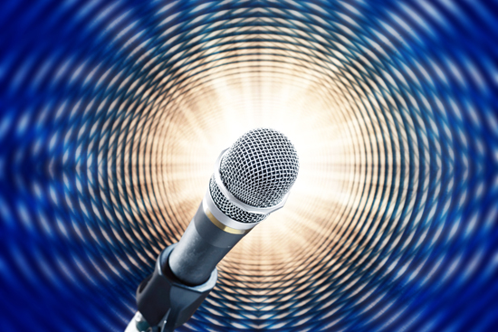 Close up of microphone on blue background simulating sound waves
