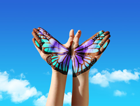 Painting of a butterfly across two hands against blue sky
